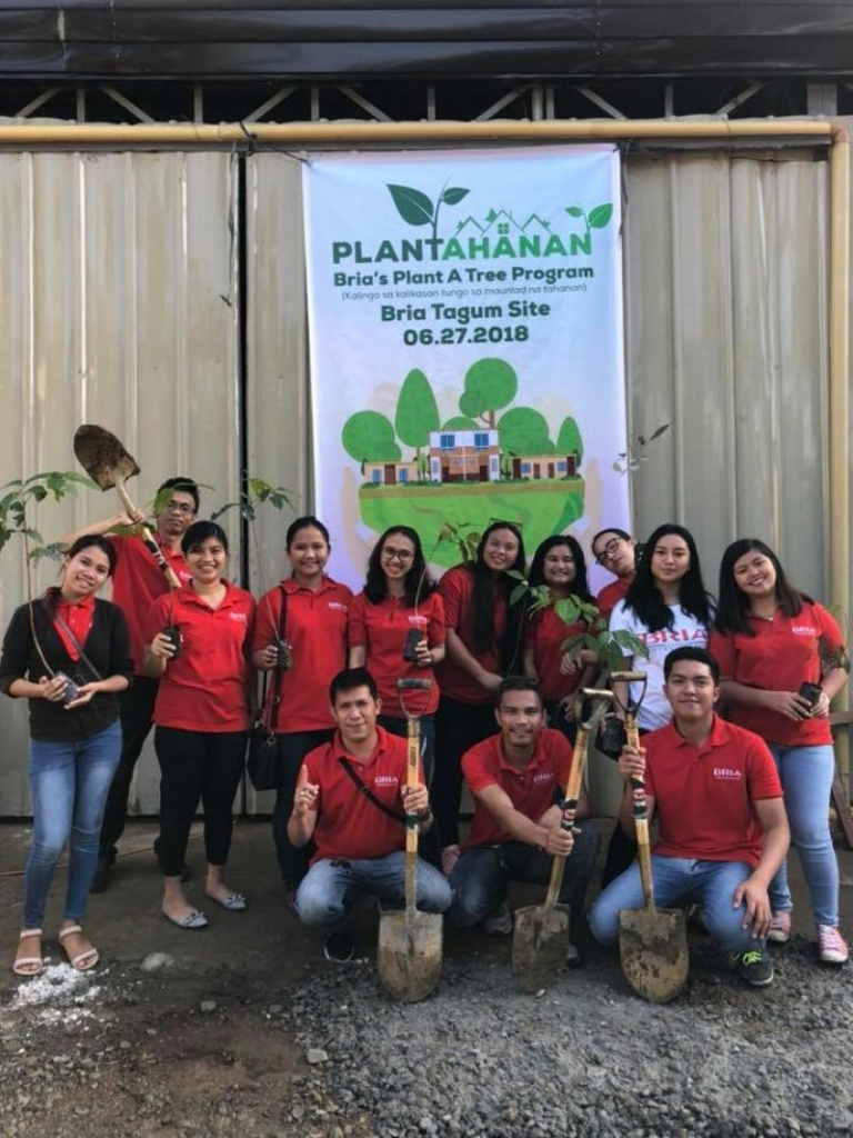 Group of people with shovels with a poster of Bria's Plant a Tree Program in the background