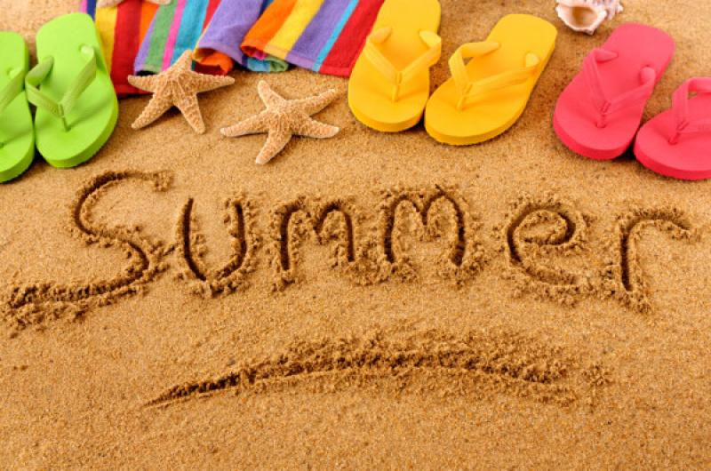 A sandy beach with the word Summer written out